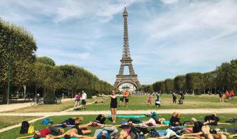 Photograph of Sasha Nelson teaching yoga in a park in Paris