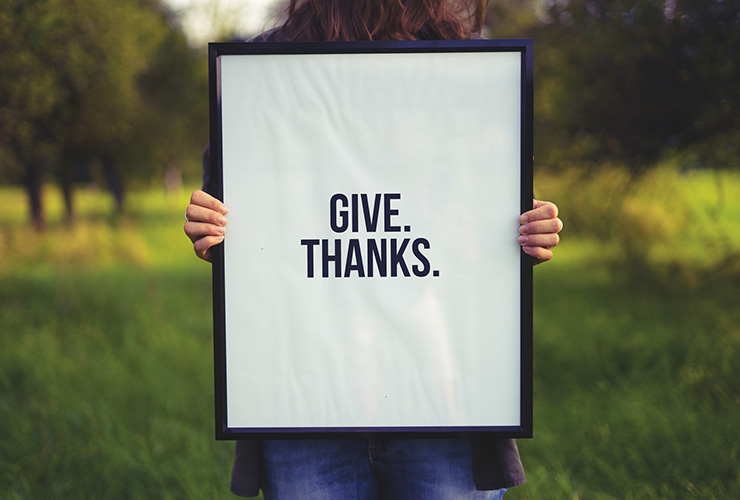 "10 Ways To Practice Gratitude To Live a Happier Life by Aimee Laurence. Photograph of a person holding up a sign that reads ""Give. Thanks."" by Simon Maage"