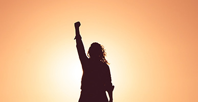 I Can't… or Maybe I Can: Releasing Our Limiting Beliefs of Our Potential by Judy Marano. Photograph of a silhouette of a woman holding her fist up in the sun