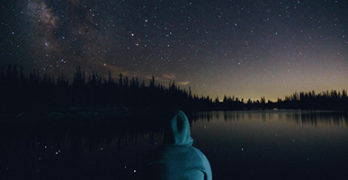 5 World Destinations for Exploring Mindfulness, Meditation and Nature by Sofia Lockart. Photograph of a man sitting by a lake looking at the starry sky by Tyson Dudley