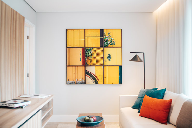 Photograph of a living room with a piece of yellow art on the wall.