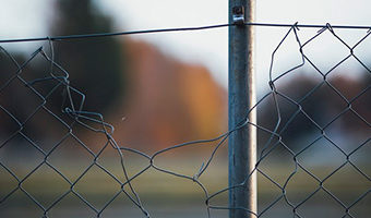 Is Your Confirmation Bias Limiting Your Mind… and Your Life? by Monica Levi. Photograph of a wire fence with a large opening in it by Markus Spiske.