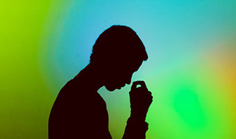It is Okay to Not Be Okay by Kass Thomas. Photograph of a silhouetted person deep in thought against a colorful background by Gift Habeshaw.